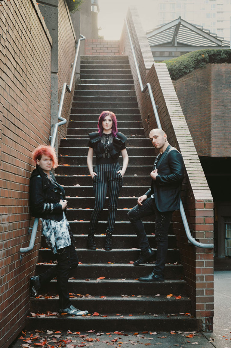 Trevor Stobbe, Bethany Stobbe, and Wade Britz standing on a staircase at dusk