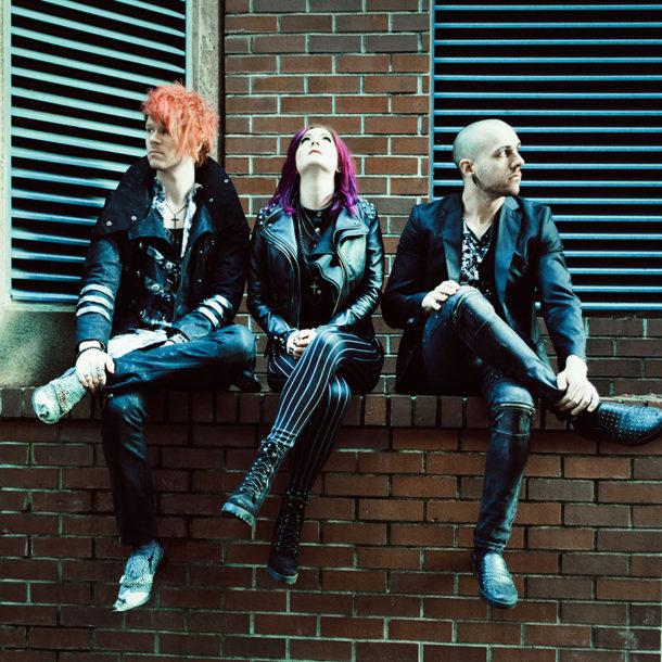 Trevor Stobbe, Bethany Stobbe, and Wade Britz sitting on a brick ledge